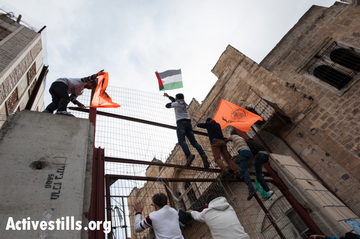Settle and concrete barriers were erected to seal off Shuhada Street, originally one of Hebron's main thoroughfares. Over 500 Palestinian businesses were forced to close their doors. (Activestills.org)